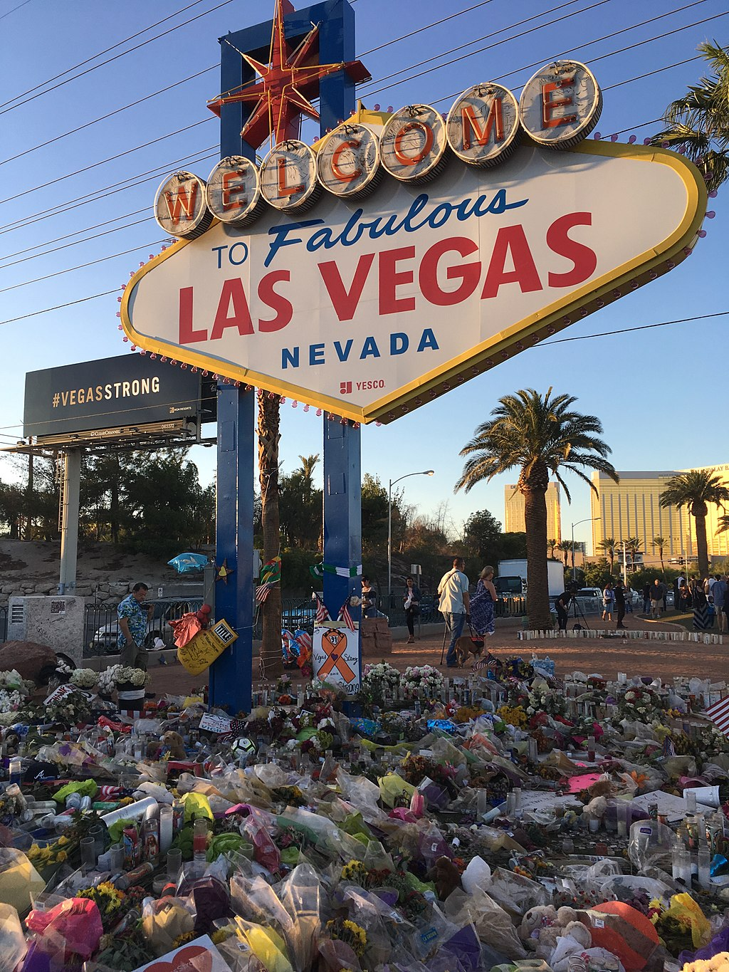 The Las Vegas Sign on The Strip covered in flowers in the wake of the 2017 Las Vegas mass shooting. Photo © Rmvisuals, CC BY-SA 4.0, via Wikimedia Commons