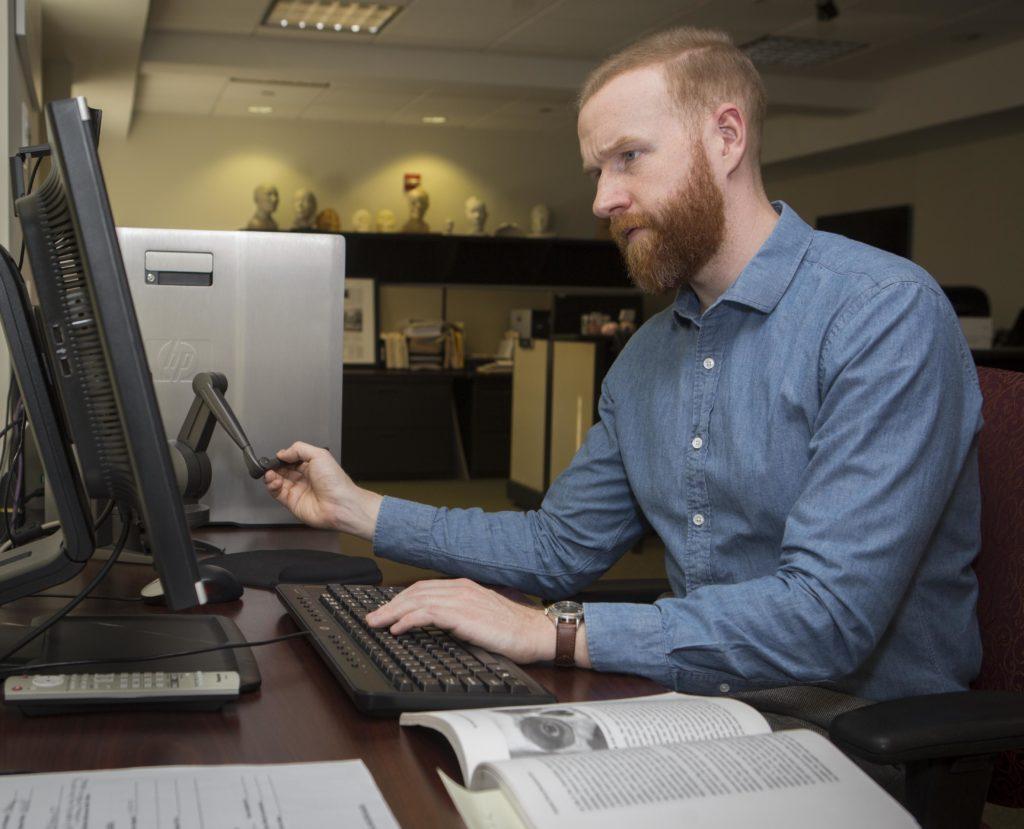 Colin McNally, supervisor of NCMEC's Forensic Imaging Unit, uses a Phantom Desktop tool to put the face back on John Parker Doe's skull. Photo credit: NCMEC Senior Multimedia Editor Sarah Baker, courtesy NCMEC