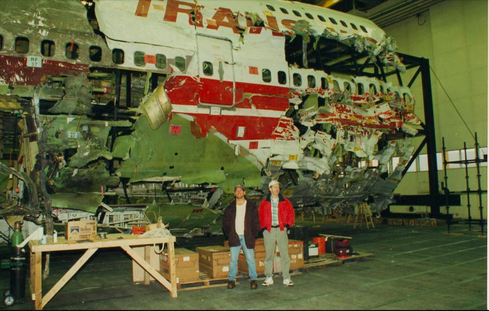 Jeff Muller (left) at Calverton Executive Airpark in Suffolk County, New York, during the TWA 800 investigation, with the reconstruction of the ill-fated Boeing 747 behind him. He spent weeks out in the Atlantic Ocean on a scallop boat, dredging the ocean floor for victims and evidence. crashed into the Atlantic Ocean near East Moriches, New York, on July 17, 1996, at about 8:31 p.m. EDT, 12 minutes after takeoff from JFK Airport en route to Rome, with a stopover in Paris. All 230 people on board died in the third-deadliest aviation accident in U.S. history. Photo courtesy Jeff Muller.
