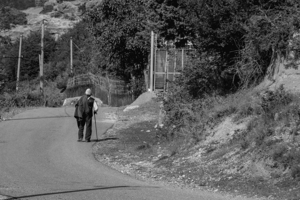 An old man walks alone along a lonely road. © Alikaj2582 | Dreamstime.com