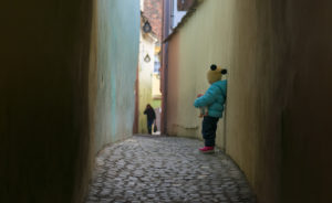 A little girl standing alone on Strada Sforii or String Street in Romania. © Tutye2001 | Dreamstime.com