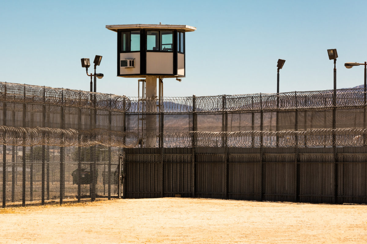 Exterior horizontal shot of desert prison yard with a guard tower in the background