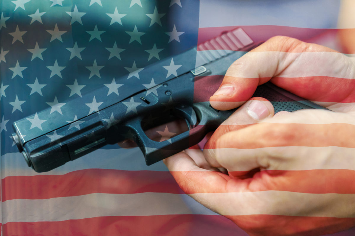 A hand of man practicing firing using a Glock gun model imposed on the American flag