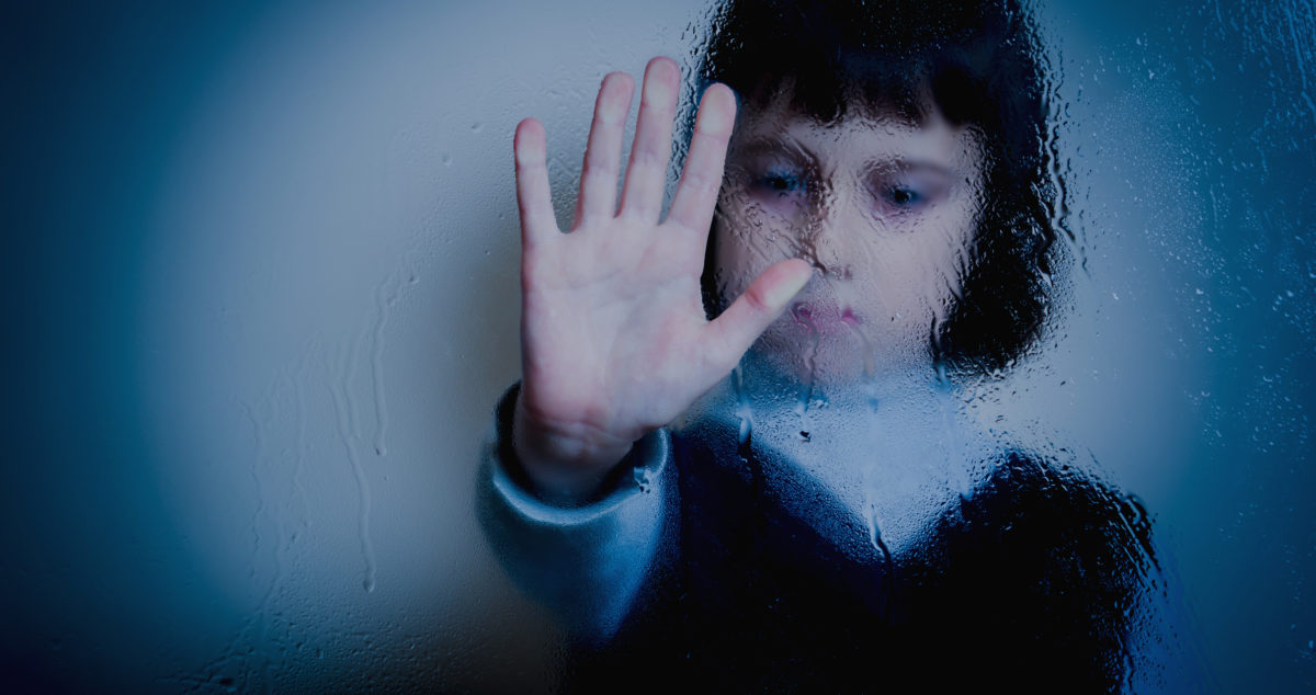 Photo of a young girl behind a glass pane showing the stop sign © Iurii Kuzo | Dreamstime.com