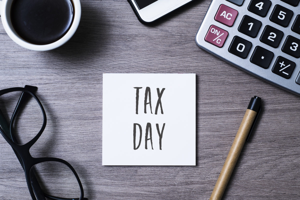 High angle view of a note with the text tax day written in it, a pair of black plastic rimmed eyeglasses, a cup of coffee, a smartphone, a pen, and an electronic calculator on a gray wooden desk © Juan Moyano | Dreamstime.com