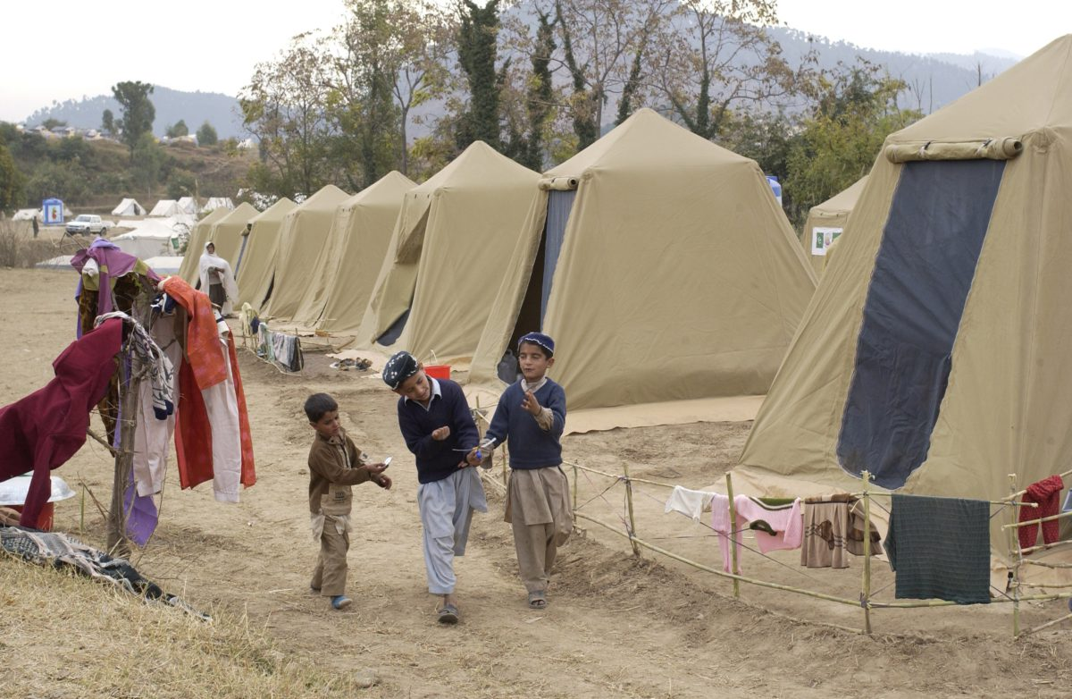 Image depicts three children at a camp in Pakistan, walking and playing. Representative image by David Mark from Pixabay
