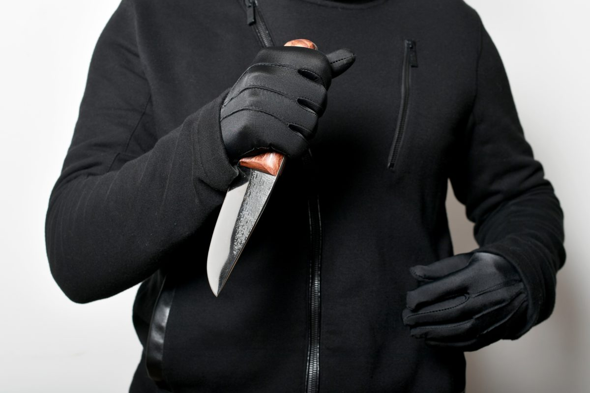 Representative image of the torso of a man dressed in black, wearing gloves and holding a sharp knife