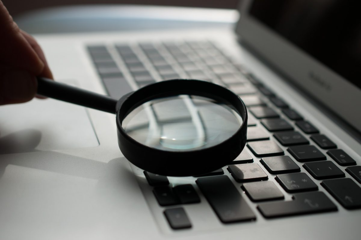 Representative black & white photo of a magnifying glass on a laptop | Photo by Agence Olloweb on Unsplash