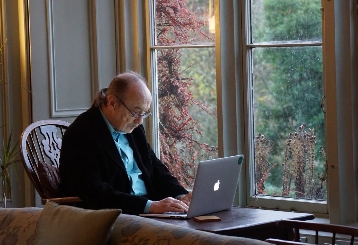 Representative image of an elderly man sitting by a window and looking at a laptop