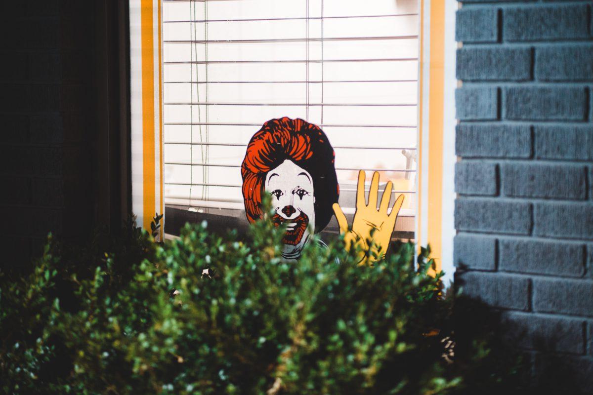 Representative image of graffiti depicting Ronald McDonald half hidden by a bush, smiling and waving