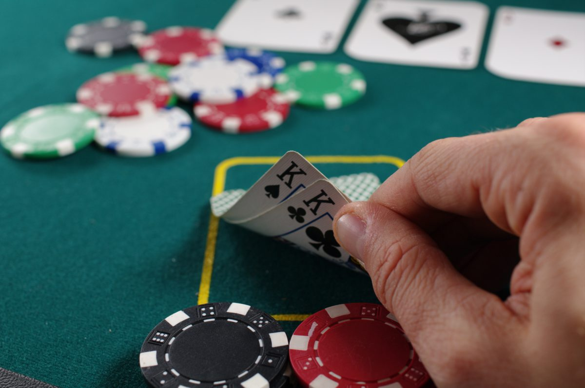 Representative image of a poker table with poker chips and a man's hand showing a pair of Kings