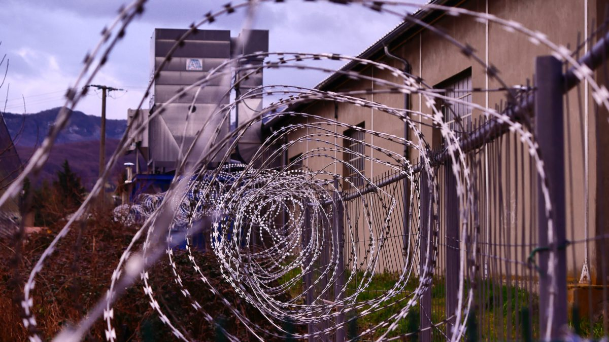 Representative image of barbed wire coils in the foreground and a prison building in the background