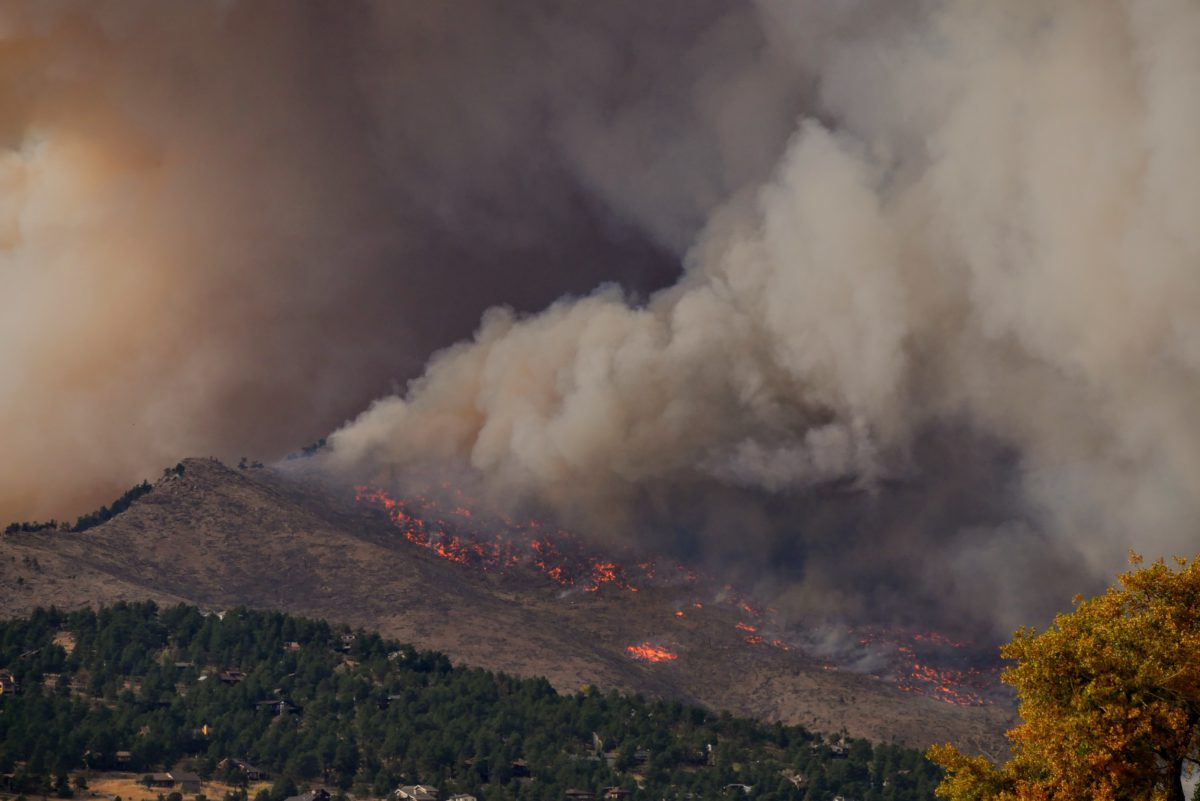 Image of a fire burning across a forested mountainside, with smoke billowing into the air