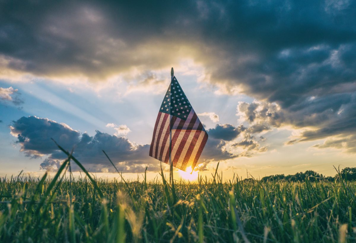 Representative photo of the USA flag on a grass field | Photo by Aaron Burden on Unsplash