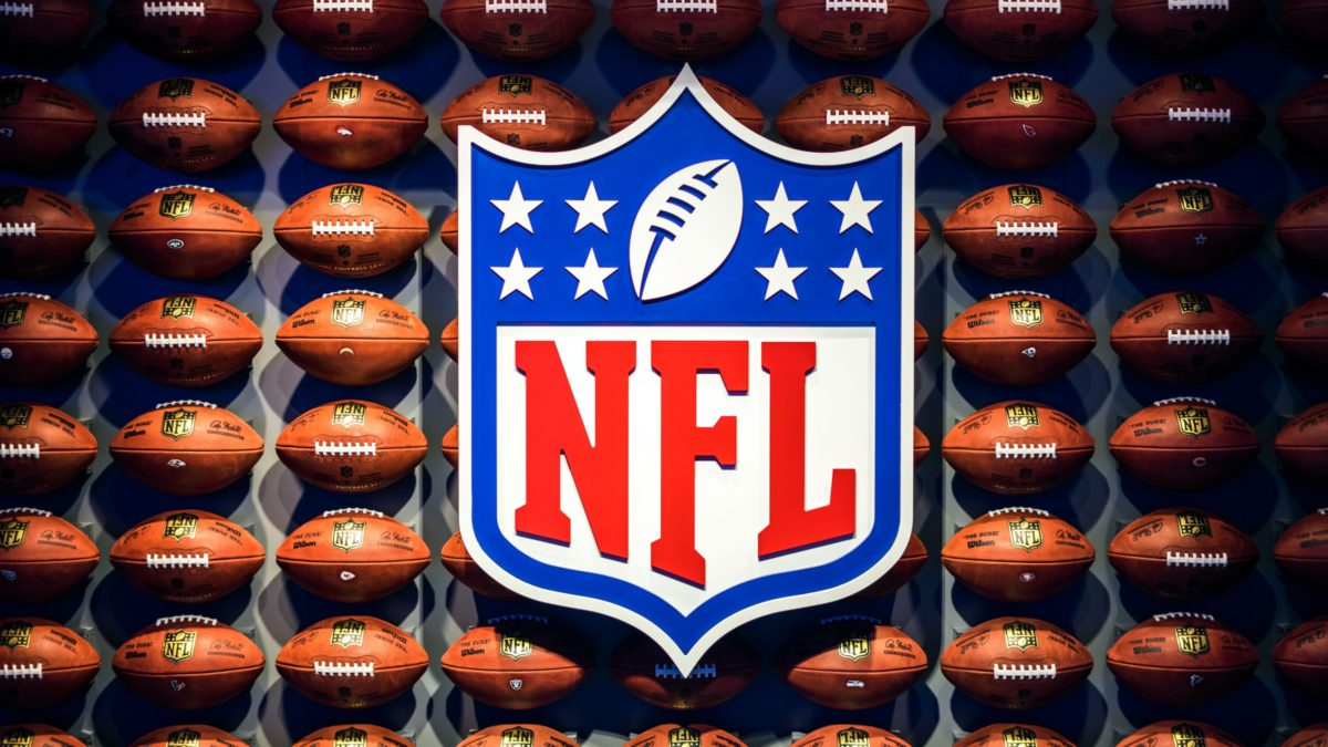 Image of the NFL logo against a backdrop of footballs | Photo by Adrian Curiel on Unsplash