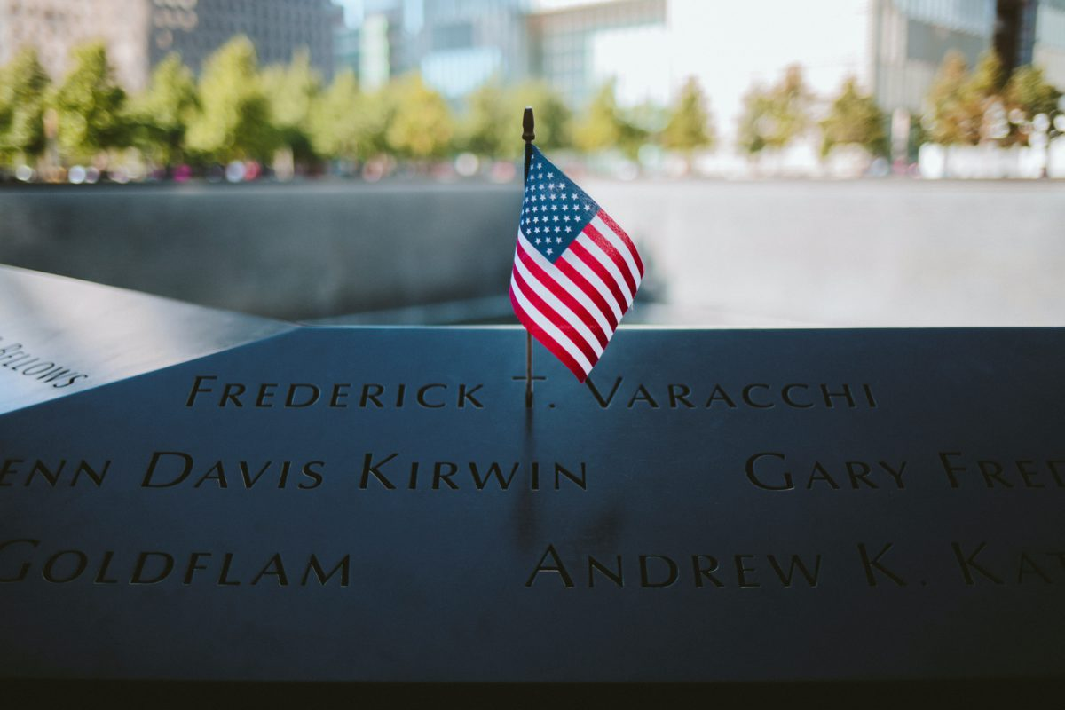 Representative image of an American flag against the backdrop of the the WTC 9/11 Memorial in New York City