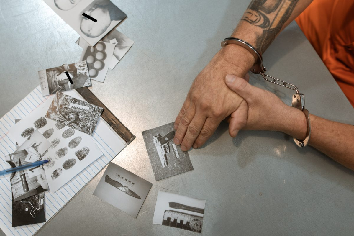 Image of a table with a person's handcuffed hands and crime scene photos
