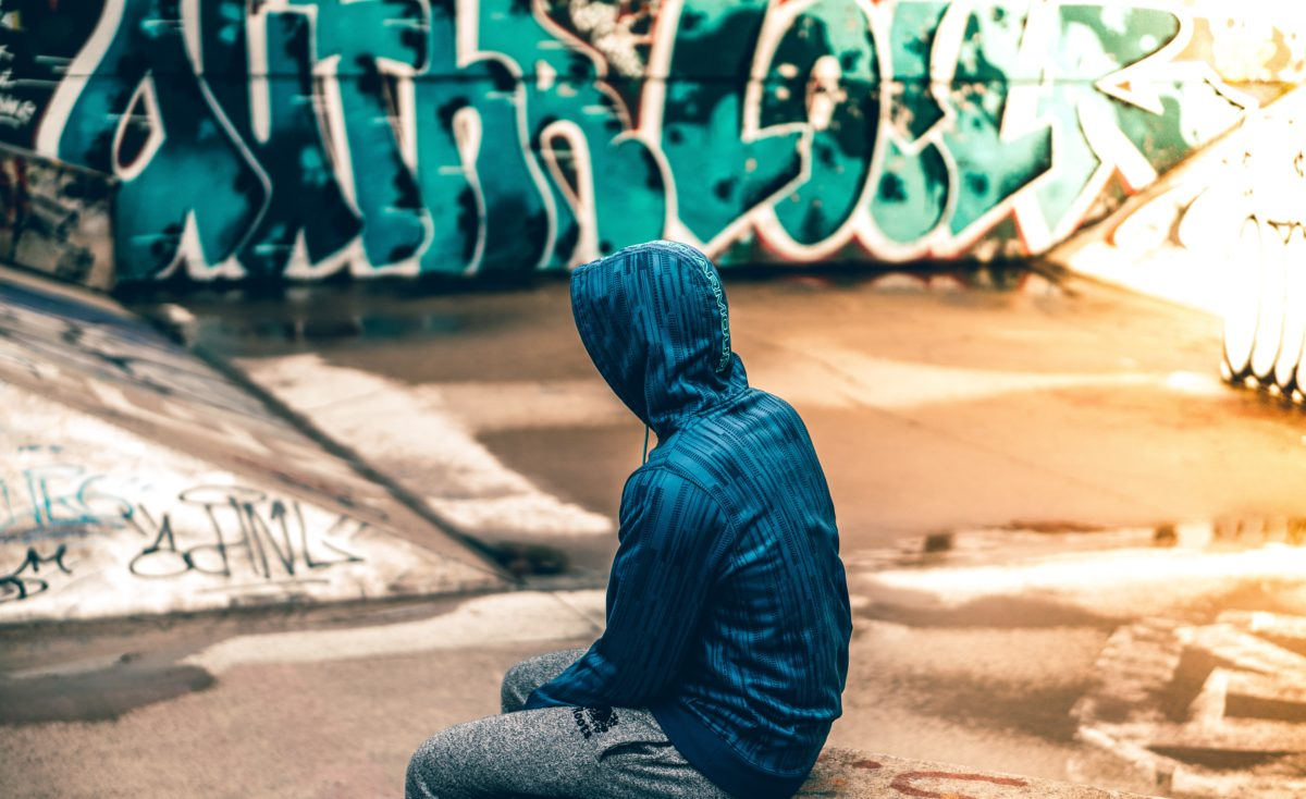 Representative image of a person wearing a sweatshirt sitting in front of a graffiti wall
