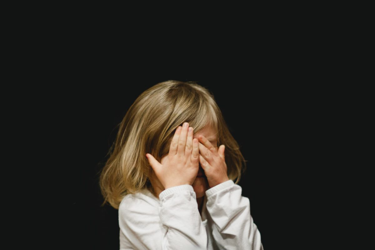 Representative photo of a little girl shutting her eyes with her hands | Photo by Caleb Woods on Unsplash