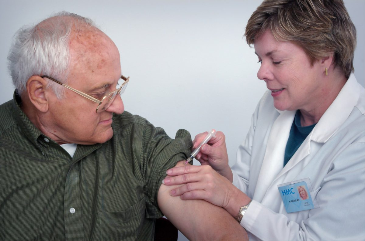 Representative photo of a home health care provider administering an injection to a senior citizen   Photo by CDC on Unsplash