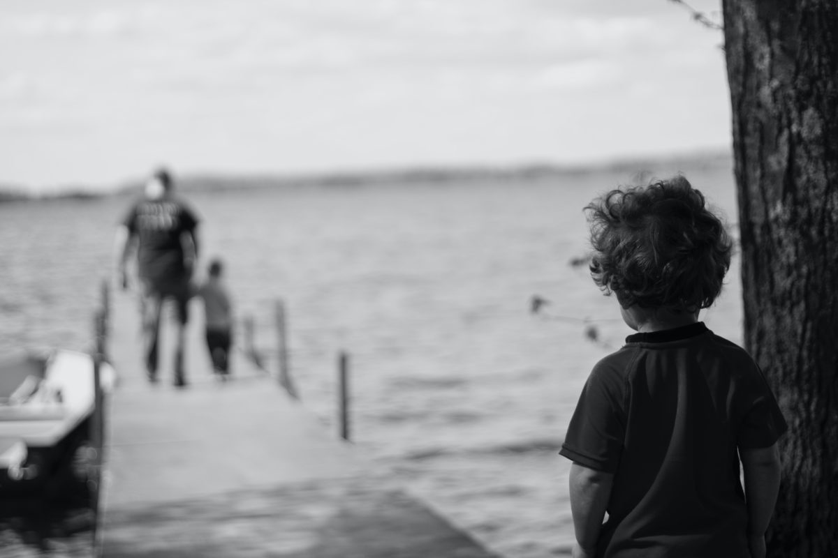 Grayscale image of a boy from a distance watching a man another boy walking on a pier.