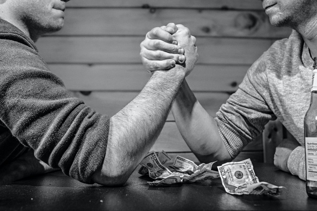 Two men arm wrestling on a table, beside a pile of dollars