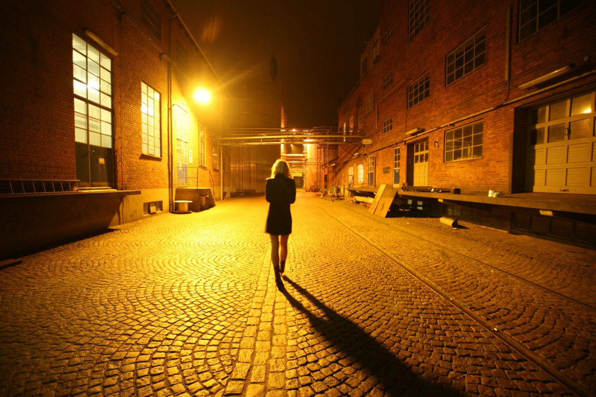 Back view of a woman walking alone on a street at night